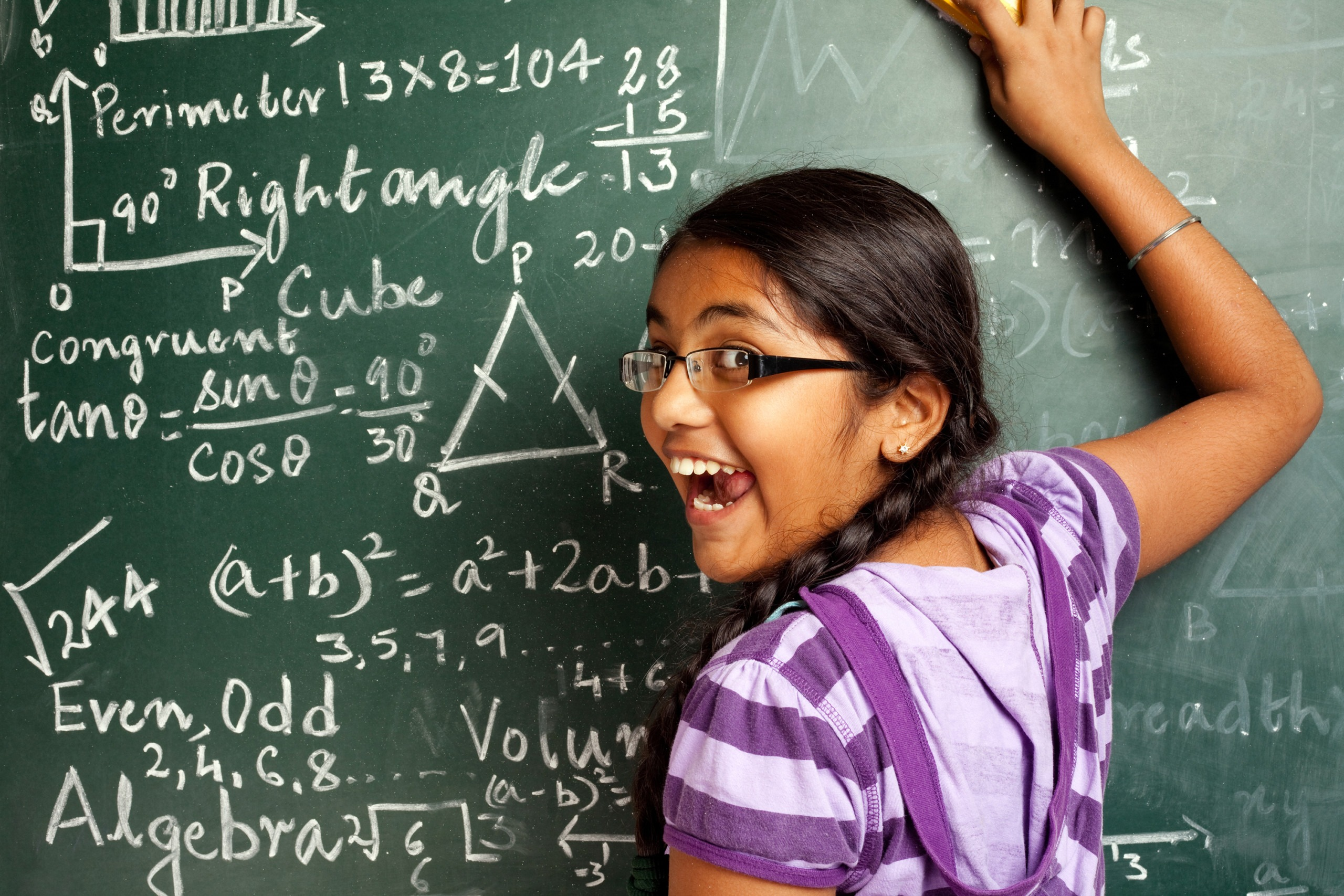 Cheerful Indian Girl Student Erasing Mathematics Problems from Greenboard