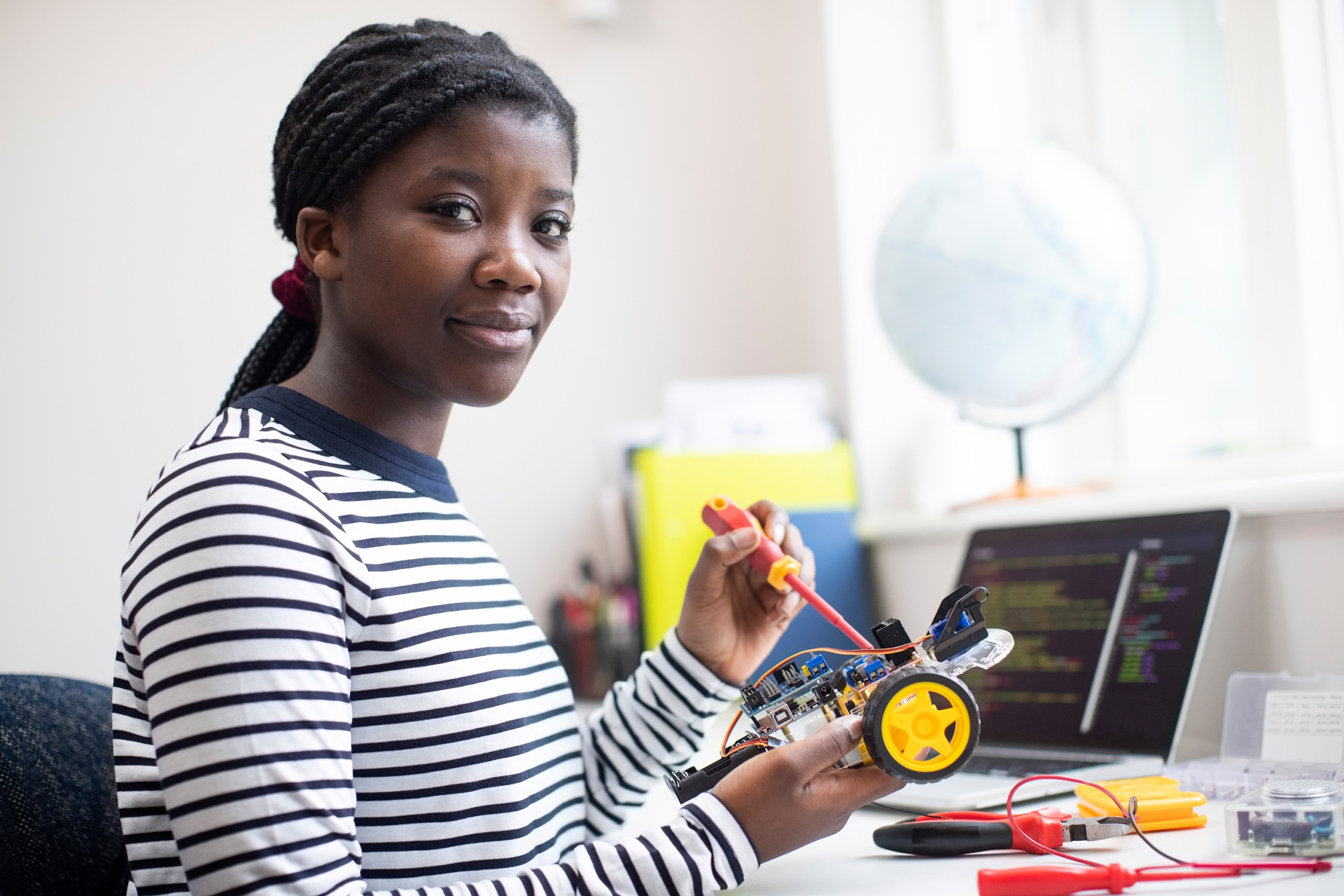 Portrait Of Female Teenage Pupil Building Robot Car In Science Lesson
